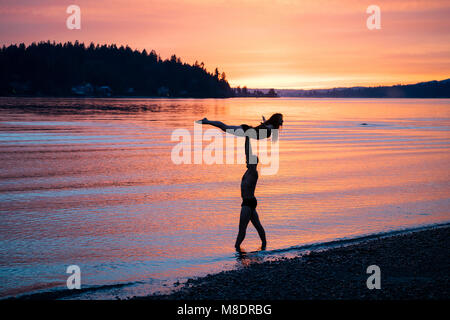 Couple practicing yoga on beach at sunset Banque D'Images