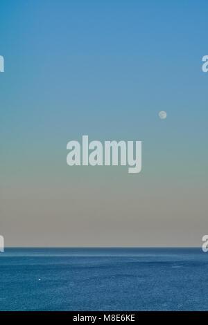 Lune sur la mer calme sur une chaude soirée Banque D'Images