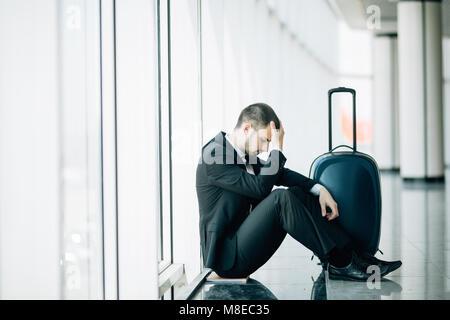 Business man sitting at the airport terminal sur le plancher avec valise vol retardé, deux mains se touchent en tête, maux de tête, attendant le voyage.