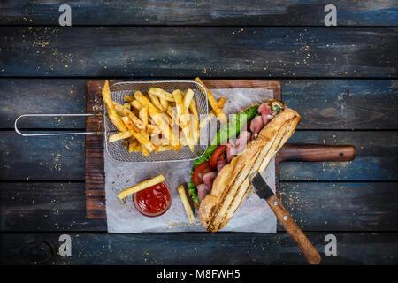 Grand sandwich pain de légumes et boeuf rôti sur planche à découper en bois Banque D'Images