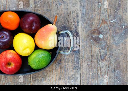 Fruits mélangés de pommes, lime, citron, poires et prunes dans le plateau métallique sur la table en bois avec copie Banque D'Images