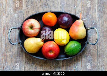 Fruits mélangés de pommes, lime, citron, poires et prunes dans le plateau métallique sur table en bois Banque D'Images
