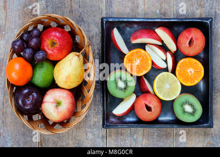 Ensemble et de tranches de fruits de la pomme, citron vert, citron, poires et prunes sur table en bois rustique Banque D'Images