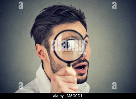 Jeune homme curieux à travers une loupe Banque D'Images