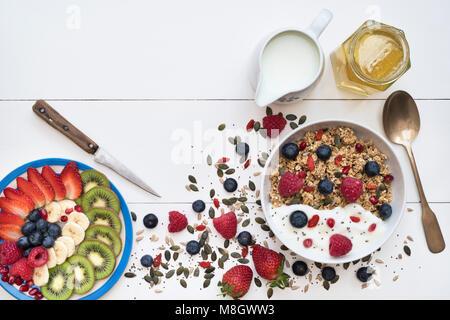 Petit-déjeuner bol de granola et une assiette de tranches de fruits avec des graines, le yogourt et le miel sur Banque D'Images