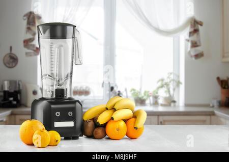Mélangeur alimentaire métal close-up avec des fruits exotiques tropic à côté de lui sur la cuisine avec arrière Banque D'Images