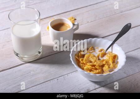Céréales flocons de maïs dans un bol, le verre de lait et de cap avec expresso. Le petit déjeuner du matin. Banque D'Images