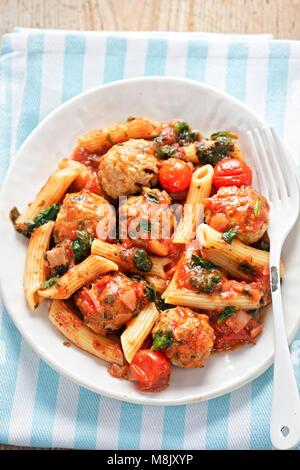 Boulettes de porc avec des pâtes, des tomates cerises, des épinards à la sauce tomate Banque D'Images