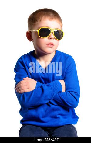 Un garçon d'une veste bleue se trouve, isolé sur fond blanc Banque D'Images