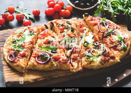 La pizza maison meubles sur planche à découper en bois. Selective focus Banque D'Images