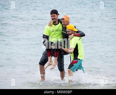 Un triathlète handicapé est aidé hors de l'eau après avoir terminé l'étape de la nage à l'ETU triathlon sprint triathlon Banque D'Images