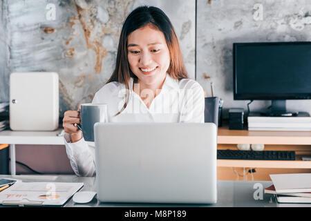 Asian businesswoman prendre une pause-café après avoir travaillé à l'ordinateur portable sur le bureau avec visage souriant, heureux de la vie de bureau concept,femme qui travaille à l'hôtel moderne