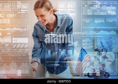 Smiling woman looking at her laptop while un robot assis à côté d'elle Banque D'Images