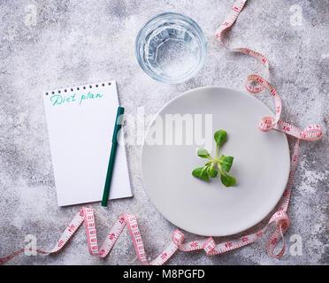 La plaque avec les feuilles de salade, d'eau et ruban à mesurer Banque D'Images