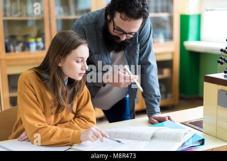 Jeune enseignant d'aider son élève en classe de chimie. L'éducation, de tutorat et de l'encouragement concept. Banque D'Images