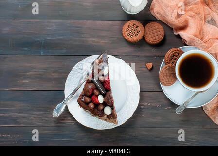 Morceau de gâteau au chocolat blanc sur assiette, tasse de café noir, jug et chocolat cookies sur la table en bois Banque D'Images