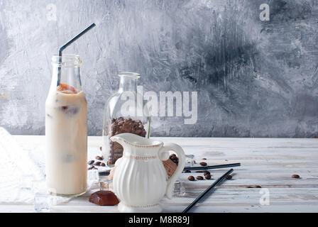 Glace café en bouteille, macarons,, morceaux de chocolat et les grains de café sur un tableau sombre Banque D'Images