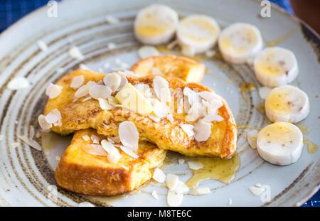 Plateau de pain doré aux bananes et sirop d'érable sur le dessus. Banque D'Images