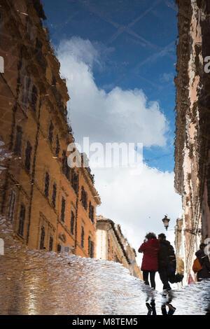 Deux personnes reflète dans une grande flaque après une douche de pluie, Rome, Italie Banque D'Images