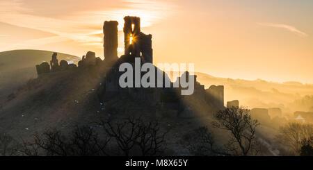 Château de Corfe, Dorset, UK. 21 mars 2018. Météo britannique. Poutres apparentes du soleil et autour de la silhouette Banque D'Images