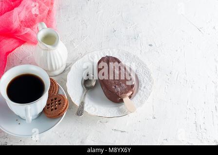 Petit déjeuner savoureux crème glacée au chocolat au lait et une tasse de café noir fort Banque D'Images