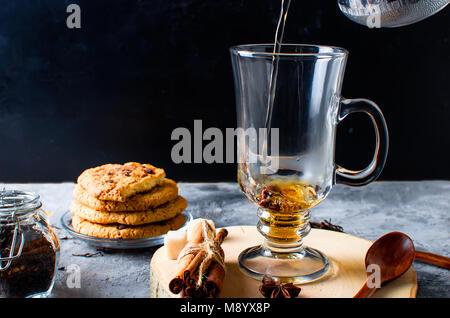 Verser dans la tasse de thé sur fond sombre, tasse de thé, biscuits, épices pour le thé. Banque D'Images