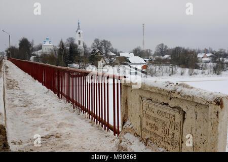 Vue sur un village avec église couverte de neige et un pont sur une petite rivière bâti à l'occasion du 50e anniversaire de l'URSS, Porechye village, TNS Banque D'Images