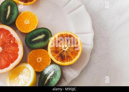 Fruits colorés sur une plaque blanche, tranches de fruits sur une table de famille Banque D'Images