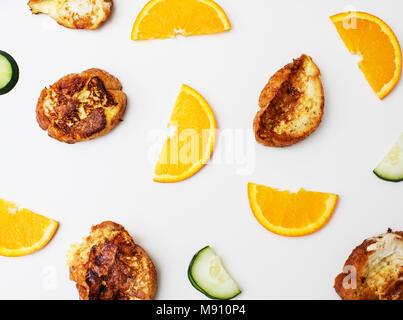 Modèle: petit-déjeuner, des tranches de pain grillé français des oranges et des concombres sur un tableau blanc dessus. Banque D'Images
