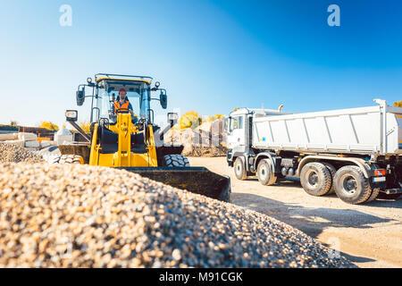 Les travailleurs qui font de la construction terrassement chargeur sur roues avec Banque D'Images