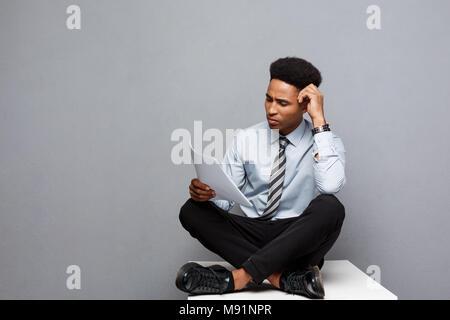 Concept d'affaires - handsome young african american businessman lecture sérieuse paperworks. Banque D'Images
