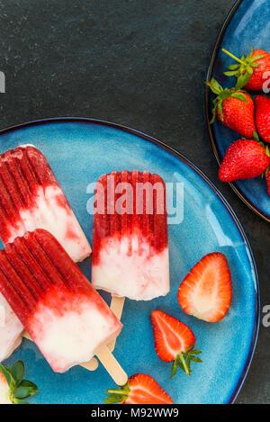 Vegan fait maison avec Popsicle Fraise Jus de fraises et le lait de coco sur fond marbre sombre. Concept des aliments en été. Vue d'en haut.