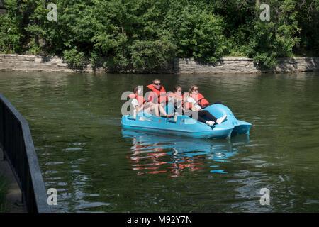 Les adolescents dans le lac des îles après le passage à travers le lac Calhoun channel dans un pédalo portant des gilets. Minneapolis Minnesota MN USA Banque D'Images
