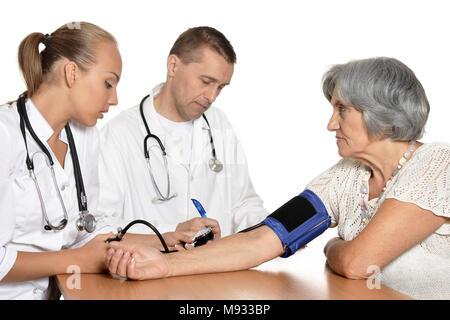Jeune infirmière la mesure de la pression artérielle à l'senior woman Banque D'Images