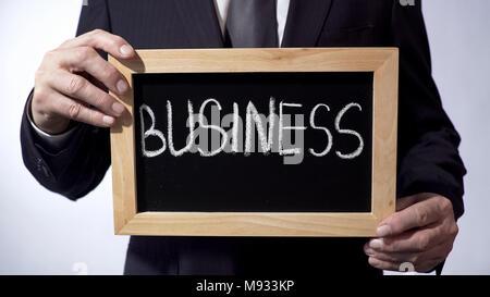 Les écrits sur tableau noir, man in suit holding sign, leadership, buts Banque D'Images