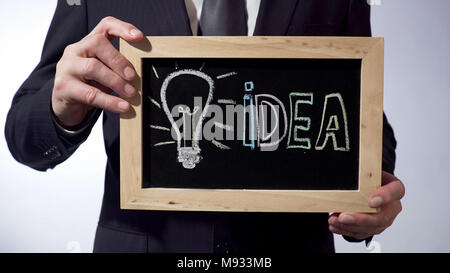 Ampoule, symbole de l'idée écrite sur tableau noir, man holding sign, motivation Banque D'Images