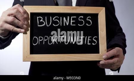 Opportunités d'affaires written on blackboard, homme in suit holding sign, concept Banque D'Images