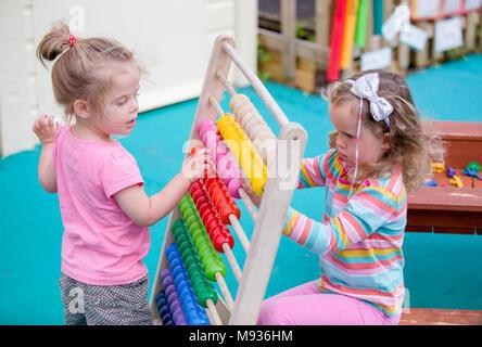 Deux jeunes filles, jouant avec un abaque à une école maternelle dans le Warwickshire, Royaume-Uni Banque D'Images