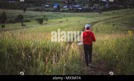 Woman in red jacket accueil marche le long de la pente country road sur le coucher du soleil