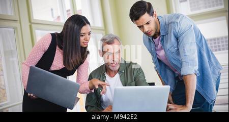 Image composite des gens d'affaires discussing over laptop Banque D'Images