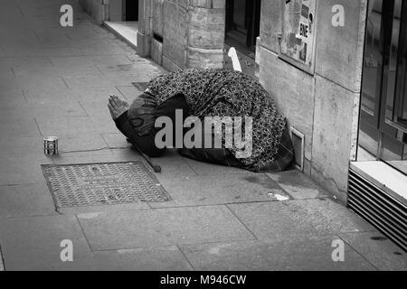 Une vieille dame de prier et de supplier pour de l'argent dans la rue