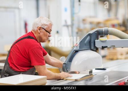 Scie à panneaux avec Carpenter et de fibres à l'usine Banque D'Images