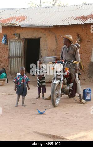 Homme sur une moto dans un village d'enfants à Banque D'Images