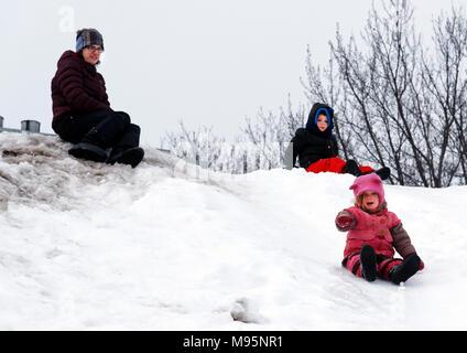 Une petite fille qui glisse sur ses fesses dans la neige, avec sa mère et son frère à sur Banque D'Images