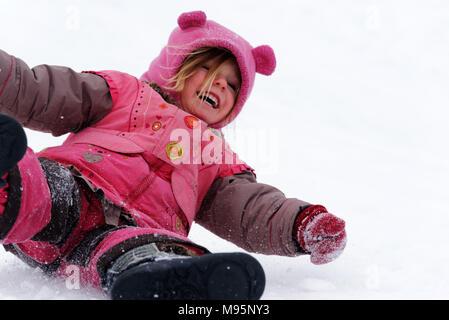 Un rire fillette de trois ans glissant sur ses fesses dans la neige au Québec Canada Banque D'Images