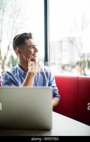 Ambiance jeune professionnel surfer sur Internet sur son ordinateur portable en cafe Banque D'Images