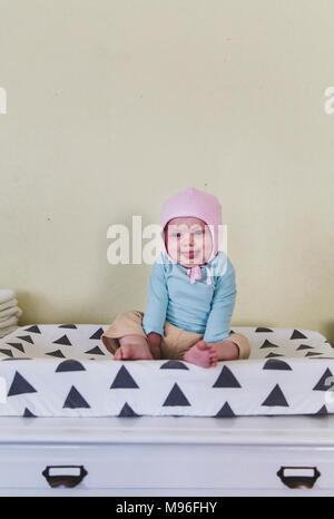 Bébé avec bonnet rose rire on bed Banque D'Images