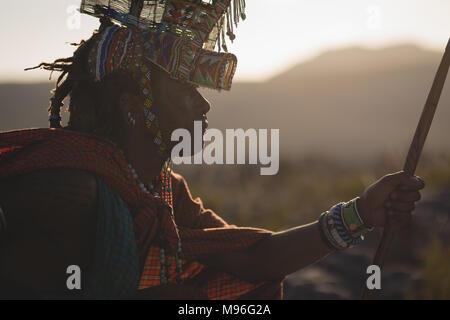 L'homme en costume traditionnel massaï assis à campagne