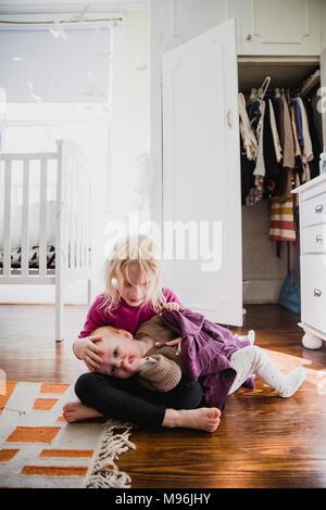 Girl avec bébé portant sur ses genoux Banque D'Images