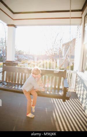 Et Bébé garçon assis sur banc oscillante Banque D'Images